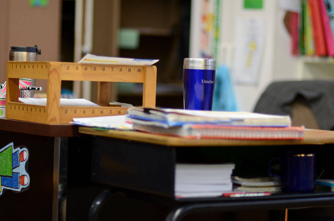 Teacher's desk with an Ursuline travel coffee mug on top