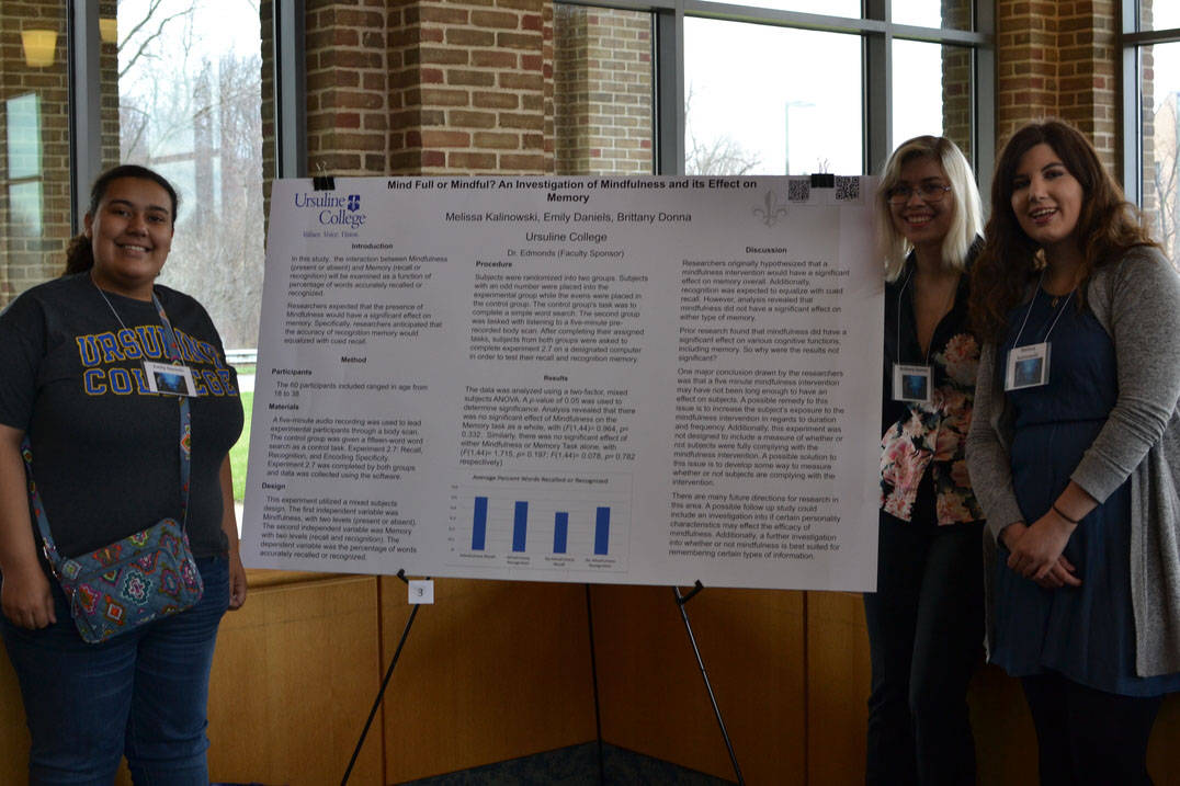 Student pose with poster at Student Research Symposium