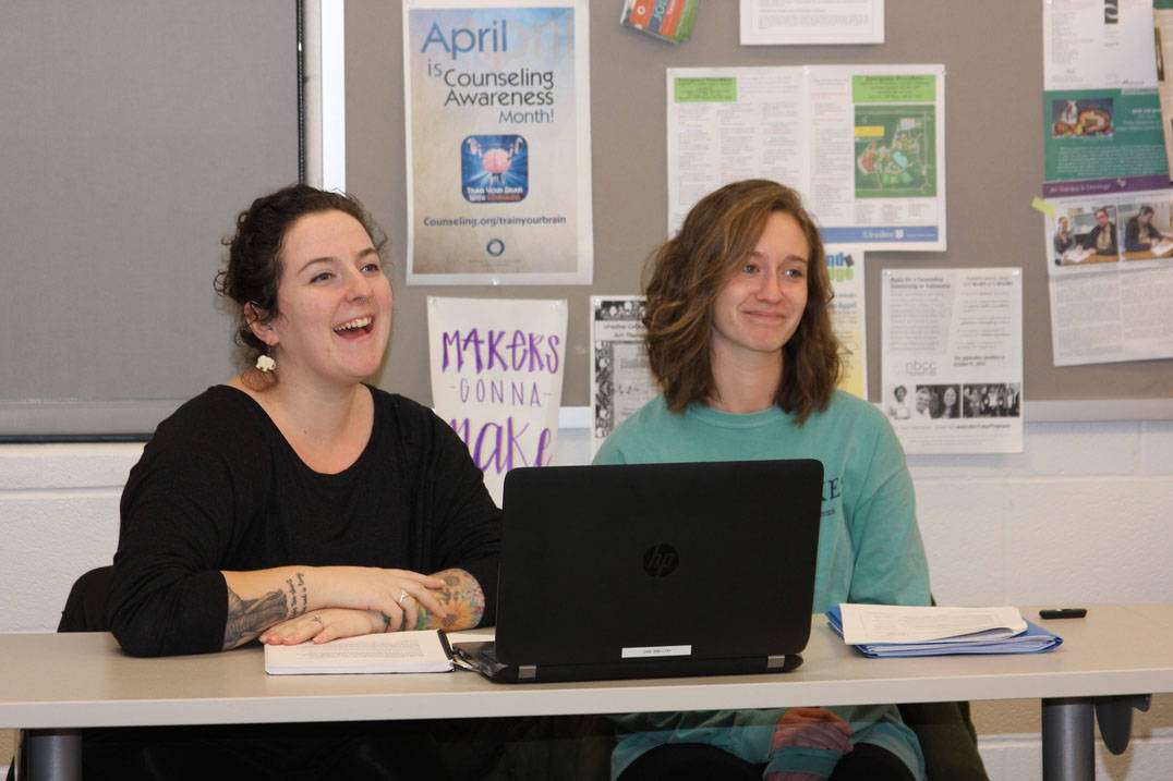 Two students smiling while listening to professor in class