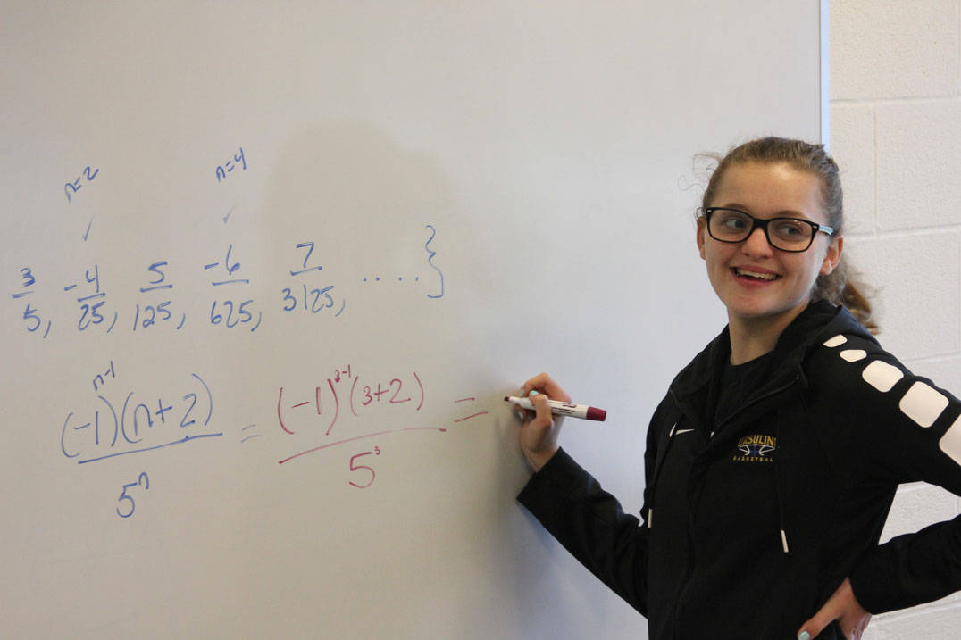 Student completes equation at the board