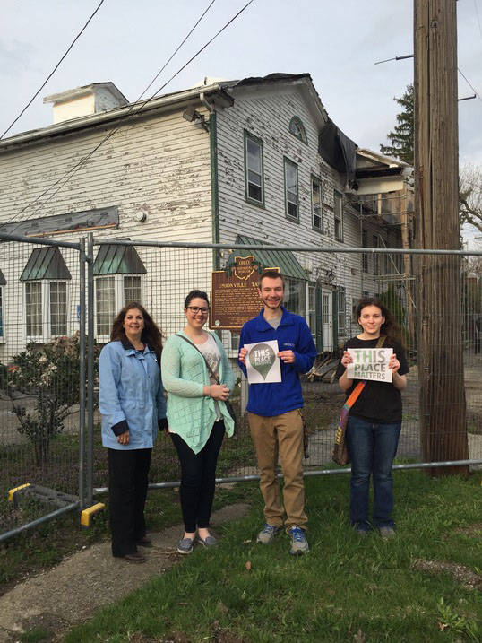 Students posing with historic preservation professor at historic landmark