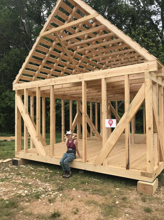 Historic preservation degree student posing with new building frame