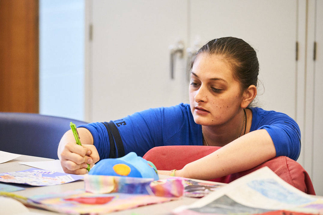 An art therapy student works intently in class.