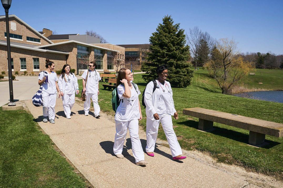Nursing students walk across campus together.