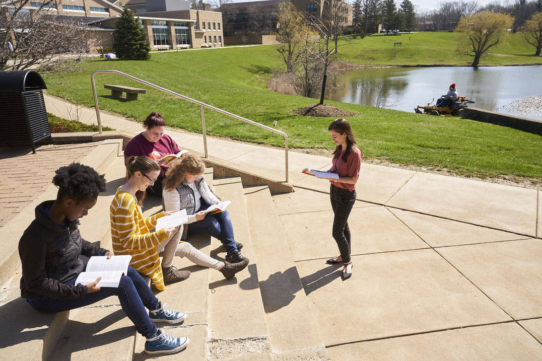 English students have book discussion outside on warm day