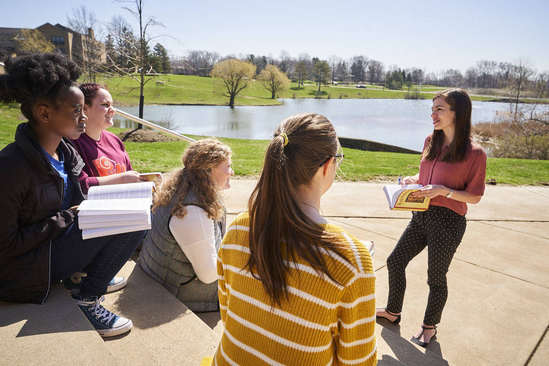English students enjoy class outside on warm day
