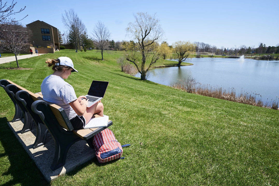 A student studies outdoors on Ursuline College campus.