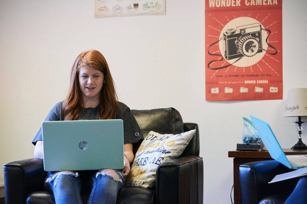 An Ursuline College student uses a laptop in a residence hall lounge.