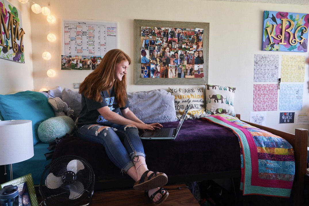 A student studying in her room in a residence hall at Ursuline College