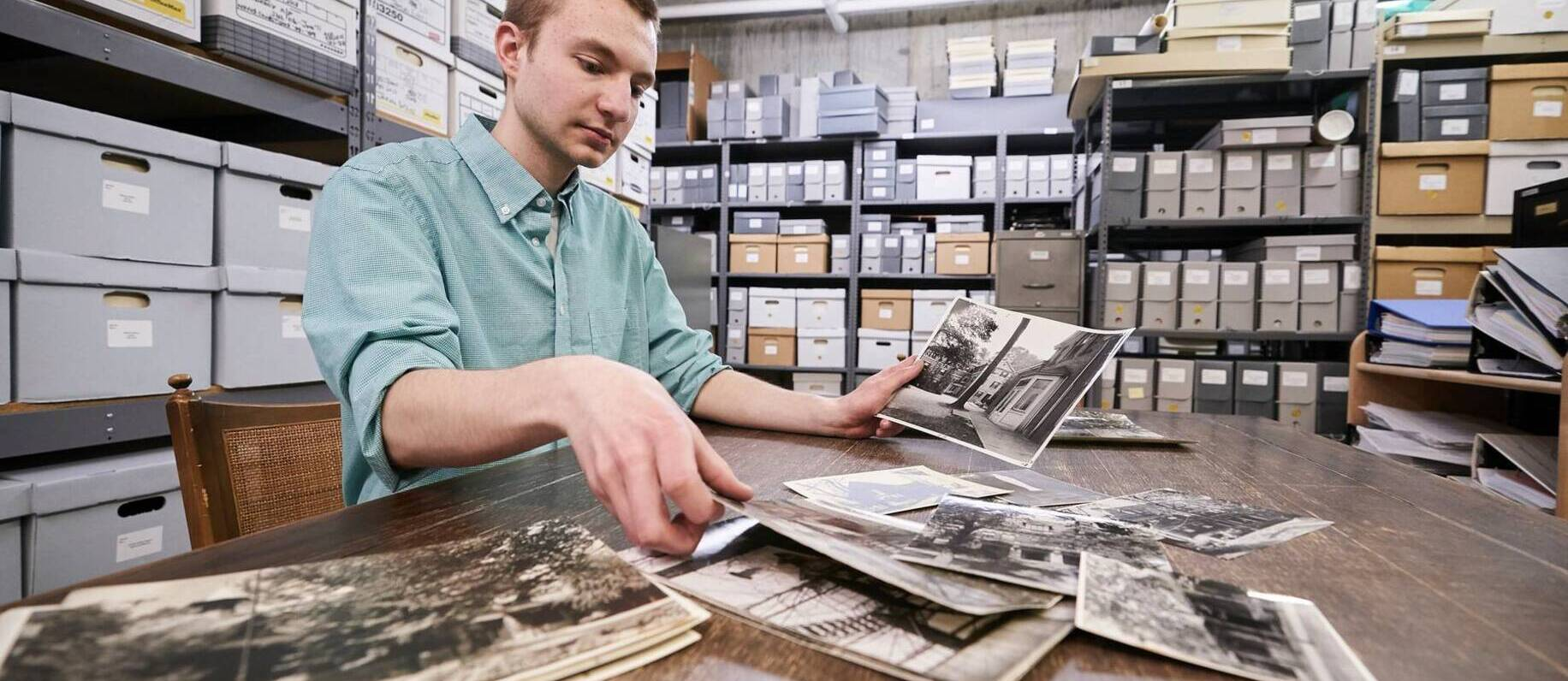 A student looks at archival photos at Ursuline College