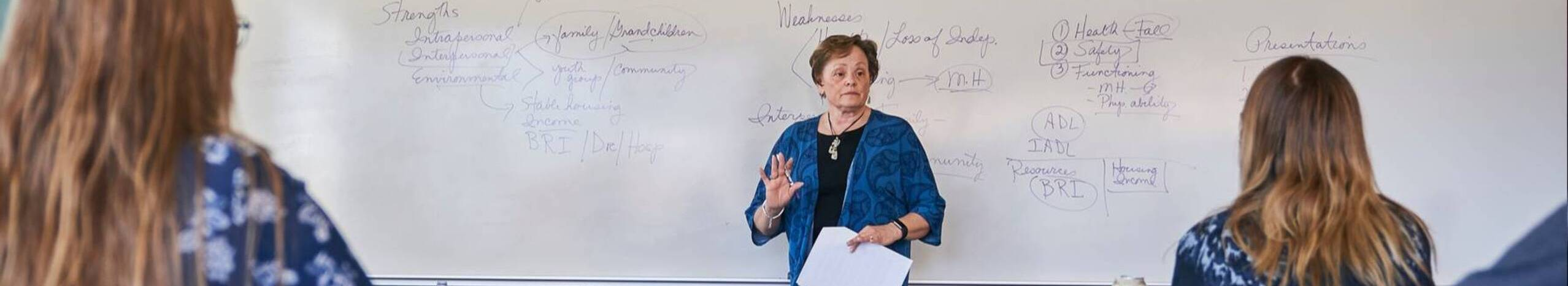 Ursuline college professor standing by white board